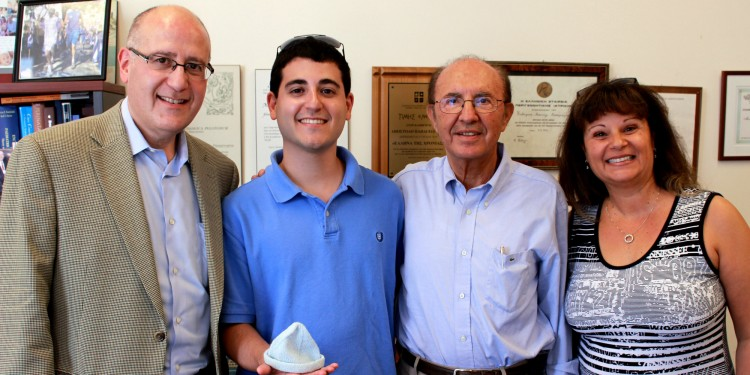 """Evan Goldstein (second from left) holds the tiny knitted cap he wore when he was born eight weeks prematurely at the JGH on Nov. 18, 1987, weighing 1,587 grams (3½ pounds). This past July, after receiving his Master's degree in Communications and Public Relations from Boston University, he visited Dr. Apostolos Papageorgiou (second from right), the JGH Chief of Pediatrics, with his parents, Lloyd and Judi. They thanked Dr. Papageorgiou for Evan's care by making a donation to The Auxiliary's Tiny Miracle Fund—co-chaired by Hela Boro, Robyn Brojde, Roz Rinzler and Lucy Wolkove—to help purchase 20 incubators for the Neonatal Intensive Care Unit. """"We've been talking for a while about helping the hospital,"""" said Mr. Goldstein, """"and when we heard about the Tiny Miracle Fund, we knew this was the time to do what we could."""" During the visit, Mrs. Goldstein also showed Dr. Papageorgiou an album of Evan's baby pictures, as well as the identification bracelet he wore in the hospital."""