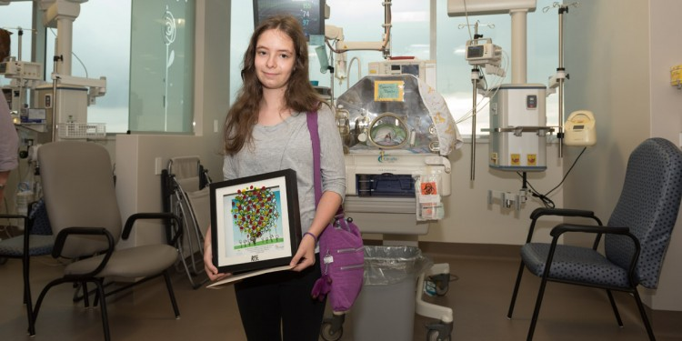 Leora Warshawsky with a framed certificate acknowledging her donation to the Neonatal Intensive Care Unit.