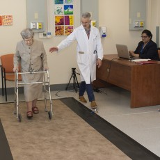 In the JGH Mobility Clinic, the gait of Jacqueline Deland, 98, is assessed as she walks on a special pressure-sensitive carpet, which is connected to a computer. Dr. Olivier Beauchet (centre) supervises the test, in which digital information is collected by Harmehr Sekhon (seated), a Clinical Research Assistant. Also providing assistance is Gerontologist Samantha Remondière.