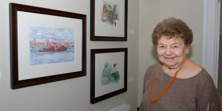 Rita Briansky, at the Hope & Cope Cancer Wellness Centre, with a painting (at left) by her late husband, Joseph Prezament, and two of her own watercolours.