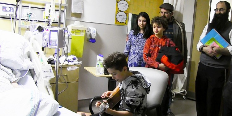 As Jeremy Gordon plays guitar for an appreciative patient, Rabbi Barak Nissim Hetsroni (right) watches the JGH event, which he organized. Accompanying him from the Shaare Zion Congregation are volunteers (from left) Tamar Durazo-Hernández, Logan Winkler, and Tamar's father, Julián Durazo-Hernández.