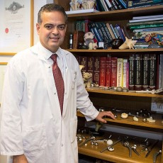 On the lower shelves of the bookcase next to Dr. John Antoniou are the kinds of implants that he uses to replace hips and knees.
