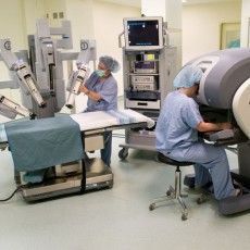 Members of staff demonstrate the components of the da Vinci Surgical System. During an operation, the patient lies on the surgical table (left), and robotic arms, each equipped with a tiny surgical tool, extend into the patient's body. The operation is performed by a surgeon at a special console (right) connected to the robot. Surgery is monitored by electronic equipment on a separate cart (centre). During an operation, the robot and its arms—but not the surgeon's console—are covered in sterile plastic sheeting.