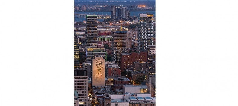 """In her winning photo in the """"A Shot of Happiness"""" competition, Vidette Uon, a nurse at Info-Santé, captured the twinkling Montreal skyline at sunset this past August. Its focal point is the enormous, illuminated Tower of Song mural, which covers the side of one building as a tribute to the late singer-composer, Leonard Cohen."""