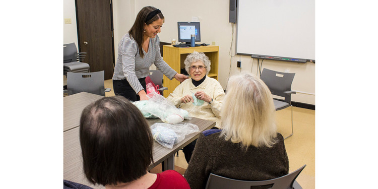 As a veteran volunteer in the psychosocial group at the Institute of Community and Family Psychiatry, 96-year-old Naomi Weiss (centre)—the oldest volunteer at the JGH—makes good use of her knitting skills to instruct and help members of the group. The group is led by Occupational Therapist Allana Goodman (standing).