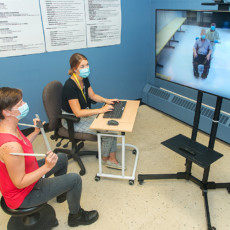 At the Constance-Lethbridge Rehabilitation Centre, Sacha Vincent-Toskin (left), an Occupational Therapist, and Michele Mercier, an Orthotic/Prosthetic Technician, connect via Zoom to a long-term care centre. During this telehealth session, they watch the screen and work with a client (seated) and with Occupational Therapist Patrice Lu to custom-design a wheelchair for the client. Mr. Lu measures him and relays the information to his colleagues, who record the data and check the screen to gain a clear understanding of the client's physical requirements.