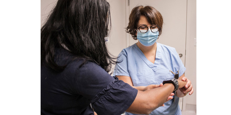 Delina Maghakian, a Nurse Clinician in the JGH Heart Failure Clinic, adjusts a wristwatch-style monitor, a type of telehealth device that helps her track her patient's vital signs remotely. (Click on any photo in this article to enlarge it.)