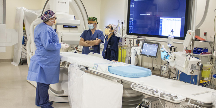 In the JGH Cardiac Catheterization Laboratory, Nurses Tracy Hodge (left) and Zaralyne Lahorra discuss clinical procedures with Dr. Nathan Messas. During treatment, the patient lies on the table and the bi plane equipment (at rear left) is brought forward. The two scanners—one at chest height and the other at head height between Ms. Hodge and Dr. Messas—can capture real-time images from two different angles and project them onto the screen at right. (Click on photo to enlarge.)